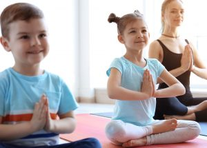 Little children and their teacher practicing yoga in gym
