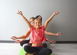Young woman having fun with kids doing yoga. Family sport concept